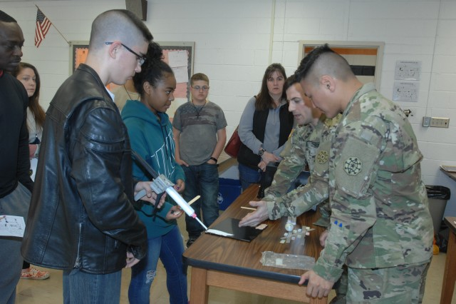 Staff Sgt. Jason Robertazzi, center, along with Staff Sgt. Dennis Kim, both CID special agents with the U.S. Army Criminal Investigation Command, as well as students in CID Senior Leaders Course, provided a forensics demonstration at Waynesville Middle School's CSI Night April 4.