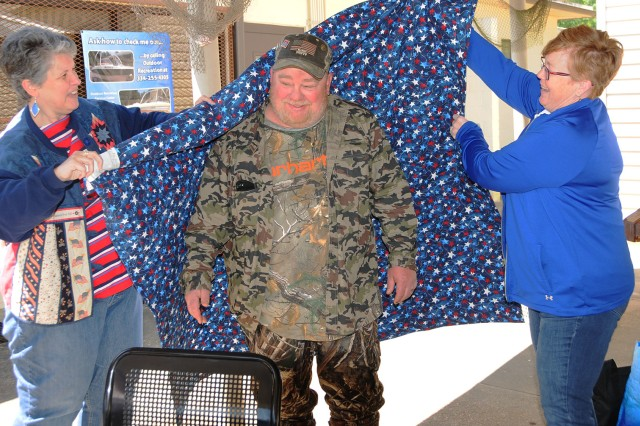 Sharon Hurd and Jacquelyn McKinstry, both of Quilts of Valor, wrap Edwin Halsey, veteran and winner of the Warrior Classic Hunt, in a Quilt of Valor, which was awarded to him during the awards ceremony April 8.