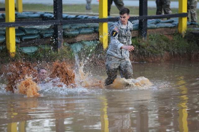 FORT BENNING, Ga. (April 13, 2018) -- First Lt. Deaven Miller, left, and Capt. Mark Gaudet, right, of Team 1 from the 1st Infantry Division, enter the water pit at Malvesti Obstacle Course. On the first day of the 2018 Best Ranger Competition, 51 teams of two Ranger-qualified U.S. military service members took on several events to test their physical endurance, mental acumen, and technical and tactical skills. The 35th David E. Grange Jr. Best Ranger Competition, an annual competition organized by the Airborne and Ranger Training Battalion, is set to determine the most elite Ranger-qualified two-athlete team of the Armed Services April 13 through 15 at Fort Benning, Georgia. (U.S. Army photo by Markeith Horace, Maneuver Center of Excellence, Fort Benning Public Affairs Office)