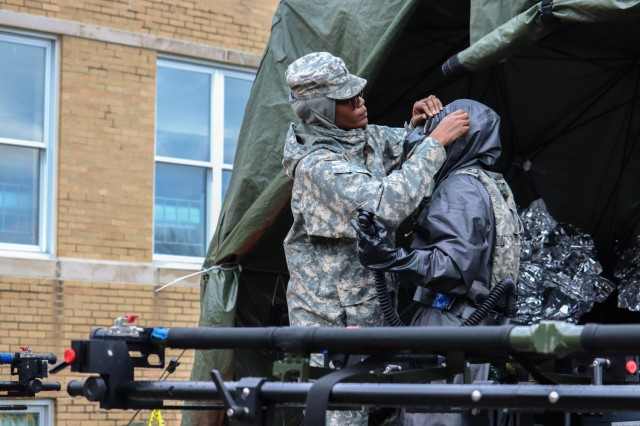 Sgt. Kecia Midette helps prepare Spc. Andrea Jones, members of the 231st Chem. Co., get into her decontamination suit to treat victims during exercise Guardian Response 18 at Muscatatuck Urban Training Center in Indiana on April 12, 2018. The exercise is linked to Vibrant Response 18 and is the multi-component U.S. Army North annual disaster response exercise is designed to validate nearly 5,200 military and government civilian personnel in the event of a Chemical, Biological, Radiological and Nuclear (CBRN) disaster.