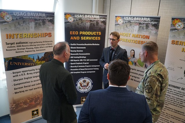 Michael Formica, director of the Installation Management command Directorate-Europe, and Col. Lance Varney, USAG Bavaria commander, talk with Felix Wolf about is experience using the apprenticeship program at USAG Bavaria during the Service Culture Center opening April 12 at Tower Barracks.