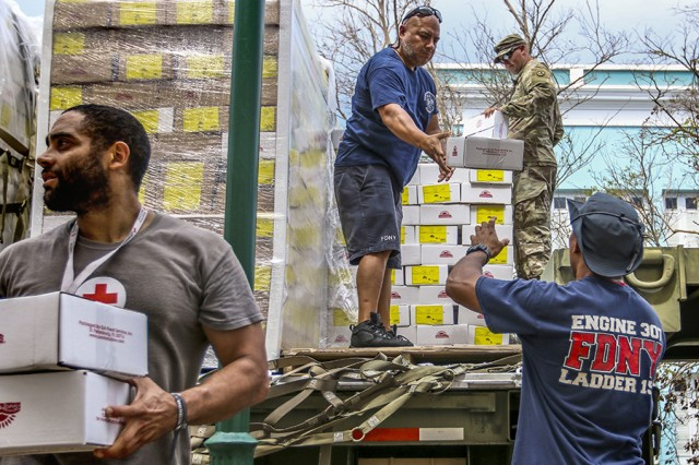 Sgt. Crew Gill, a military police officer assigned to the 3rd Expeditionary Sustainment Command, firefighters from the Fire Department of the City of New York, and a Red Cross member help unload meals ready-to-eat from a military flatbed on Oct. 2, 2017, in Vieques, Puerto Rico.