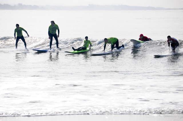 CAPITOLA, California -- Disabled veterans (in green shirts) and Operation Surf instructors take a curl into the beach here March 25.