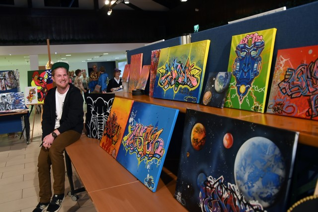"""GARMISCH-PARTENKIRCHEN, Germany (April 16, 2018) - Tim Waldmann, a contractor who works at the George C. Marshall European Center for Security Studies, showcases his and his son's """"street-art"""" made with spray paint, markers and stencils at the 4th Annual Garmisch Community Art Show held April 14 at the Pete Burke Community Center on Artillery Kaserne. (Marshall Center photo by Christine June)"""