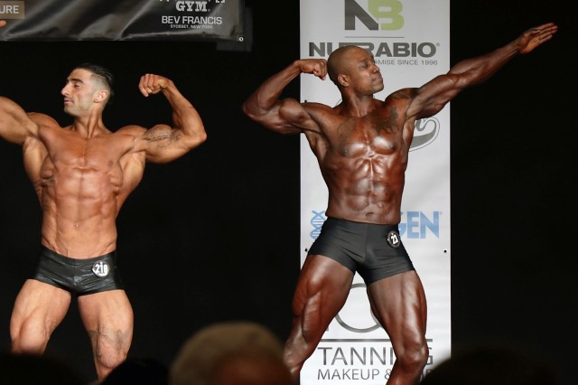 Capt. Kevon Reid (right), an Observer Coach/Trainer assigned to 174th Infantry Brigade, performs one of the mandatory poses during the 2018 Steve Stone Metropolitan Bodybuilding Championships in Teaneck, New Jersey Mar. 31. Capt. Reid, in his competitive debut, placed second in the Men's Classic Physique division. (Courtesy Photo)