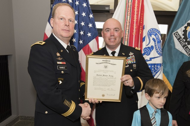 Maj. Gen. Duane Gamble, commanding general, U.S. Army Sustainment Command, presents a promotion certificate to Chief Warrant Officer 5 Jeff Lein, senior food advisor, Installation Logistics Directorate, ASC, during a promotion ceremony March 30 in the foyer of the U.S. Army Sustainment Command Headquarters, Building 390, Rock Island Arsenal, Illinois. (Photo by Kevin Fleming, ASC Public Affairs)