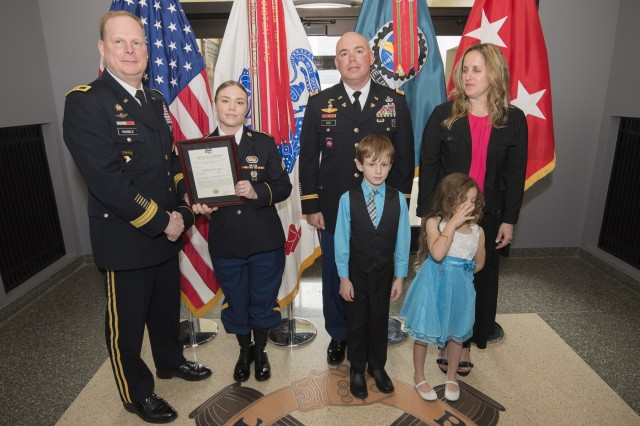 Maj. Gen. Duane Gamble, commanding general, U.S. Army Sustainment Command, presents a promotion certificate to Sgt. Kaitlin Reyes during a promotion ceremony March 30 in the foyer of the ASC Headquarters, Building 390, Rock Island Arsenal, Illinois. Reyes was promoted the same day as her father as she transitions to a new position at the Headquarters and Headquarters Company, Group Support Battalion, 5th Special Forces Group, Fort Campbell, Kentucky.