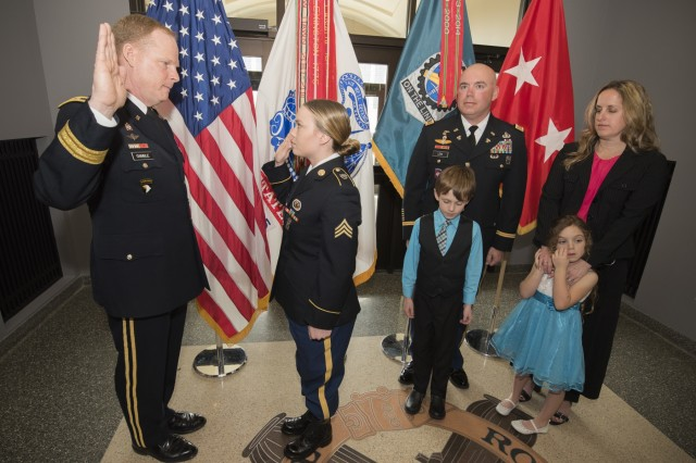 Maj. Gen. Duane Gamble, commanding general, U.S. Army Sustainment Command, administrators the oath of enlistment to Sgt. Kaitlin Reyes during her promotion ceremony March 30 in the foyer of the ASC Headquarters, Building 390, Rock Island Arsenal, Illinois. Reyes was promoted the same day as her father as she transitions to a new position at the Headquarters and Headquarters Company, Group Support Battalion, 5th Special Forces Group, Fort Campbell, Kentucky.