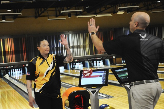 Rose Aguilar, the woman's individual title winner, gives a high five to Airman James McTaggart during the king and queen match of the Armed Forces Bowling Championship April 16 at the TenStrike Bowling Center. McTaggart won the match and led the Air Force men to the team title.  Aguilar led the Army team to the women's crown.