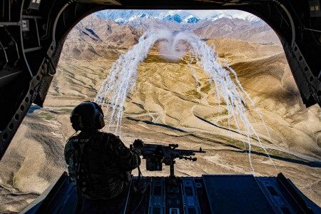 A U.S. Army crew chief assigned to Task Force Brawler, flying on board a CH-47F Chinook, observe the successful test of threat countermeasures during a training flight in Afghanistan, March 14, 2018. The Army crews and Air Force Guardian Angel teams conducted the exercise to build teamwork and procedures as they provide joint personnel recovery capability, aiding in the delivery of decisive air power for U.S. Central Command.
