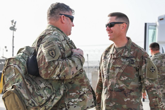 Maj. Patrick Devine, right, chaplain, Train, Advise and Assist Command-South and 2nd Infantry Brigade Combat Team, 4th Infantry Division, greets retired Staff Sgt. John Hosea, a native of Las Vegas, Nevada, April 5, 2018, during Operation Proper Exit on Kandahar Airfield, Afghanistan.