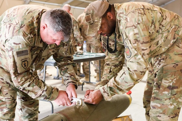 Staff Sgt. Mackel Stafford, right, weapon air advisor, Train, Advise and Assist Command-Air, helps retired Staff Sgt. John Hosea, left, a native of Las Vegas, Nevada, build a bomb for the A-29 Super Tucano light-attack aircraft, April 5, 2018, during Operation Proper Exit on Kandahar Airfield, Afghanistan.