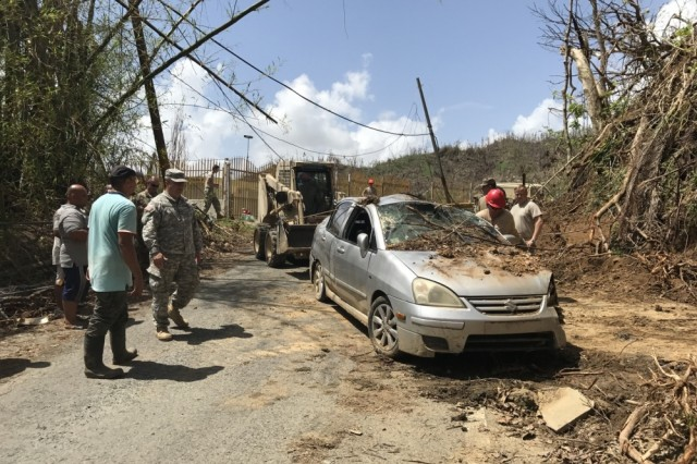 South Carolina Army National Guard soldiers work to remove dirt and debris from the driveways for residents of Talante, Puerto Rico, Oct. 8, 2017. The homes had been blocked in and surrounded by debris since Hurricane Maria hit the island.