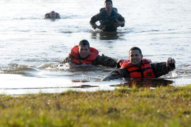 Staff Sgt. Carlos Mercado (right), a Delta Company, 1st Battalion, 505th Parachute Infantry Regiment, 3rd Brigade Combat Team paratrooper, and Staff Sgt. Christopher Hart (left), a Charlie Company, 1st Battalion, 508th Parachute Infantry Regiment, 3rd Brigade Combat Team paratrooper, prepares to exit Victory Pond during the 2018 Best Ranger Competition at Fort Benning, Georgia on Apr. 13. During the Victory Pond Swim, competitors had to keep their heads above water for the entire swim across the lake.