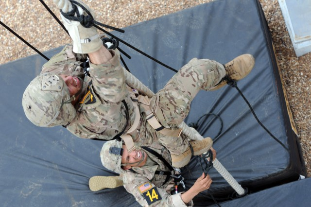 Staff Sgt. Christopher Hart (above), a Charlie Company, 1st Battalion, 508th Parachute Infantry Regiment, 3rd Brigade Combat Team paratrooper, climbs as Staff Sgt. Carlos Mercado (below), a Delta Company, 1st Battalion, 505th Parachute Infantry Regiment, 3rd Brigade Combat Team paratrooper, watches during the Dual-Tower Challenge lane of the Day Stakes portion of the 2018 Best Ranger Competition at Fort Benning, Georgia on Apr. 14. In sequential order, teams had to prepare prusik stirrups, climb more than three stories, rappel, climb a caving ladder, fast-rope and correctly tie five military knots to successfully complete the lane.