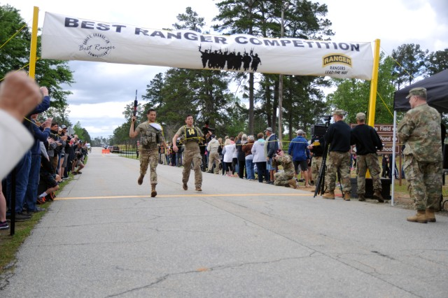 Staff Sgt. Carlos Mercado (center, left) and Staff Sgt. Christopher Hart (center, right), both 3rd Brigade Combat Team paratroopers, cross the finish line of the Final Buddy Run event during the 2018 Best Ranger Competition at Fort Benning, Georgia on Apr. 15. The Final Buddy Run was the third event of day three and final event of the competition. Mercado and Hart finished the 2018 BRC in 14th place.