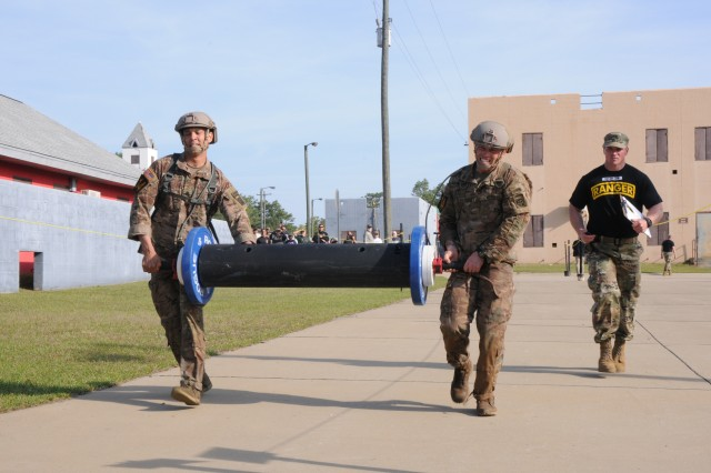 Staff Sgt. Carlos Mercado (left) and Staff Sgt. Christopher Hart (center), both 3rd Brigade Combat Team paratroopers, carry a log bar weighing more than 160lbs during the Urban Obstacle Course portion of the 2018 Best Ranger Competition at Fort Benning, Georgia on Apr. 13. The Urban Obstacle Course tested competitors as they tactically maneuvered through buildings and an urban environment.
