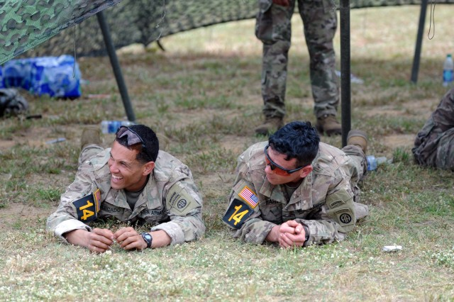 Staff Sgt. Carlos Mercado (left) and Staff Sgt. Christopher Hart (right), both 3rd Brigade Combat Team paratroopers, relax inside the holding area before starting the mystery event of the Day Stakes portion of the 2018 Best Ranger Competition at Fort Benning, Georgia on Apr. 14. The mystery event consisted of engaging various targets with multiple types of firearms at separate stations while moving to each station with a medical simulation dummy.