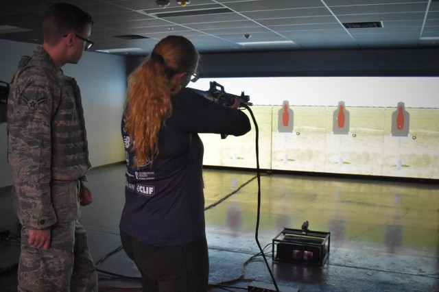 Aided by Air Force personnel, Patty Beltram, Peoria School District, engages targets at the Engagement Skills Trainer 2000 simulator, April 10, Fort Huachuca, Ariz. Beltram was one of 15 attendees from the Phoenix Recruiting Battalion's Educators Tour for 2018. The purpose of the two-day tour was to provide a comprehensive orientation and overview of Fort Huachuca for the attendees, who included teachers, superintendents and school counselors from the battalion area of influence. (U.S. Army Photo by Alun Thomas, USAREC Public Affairs)