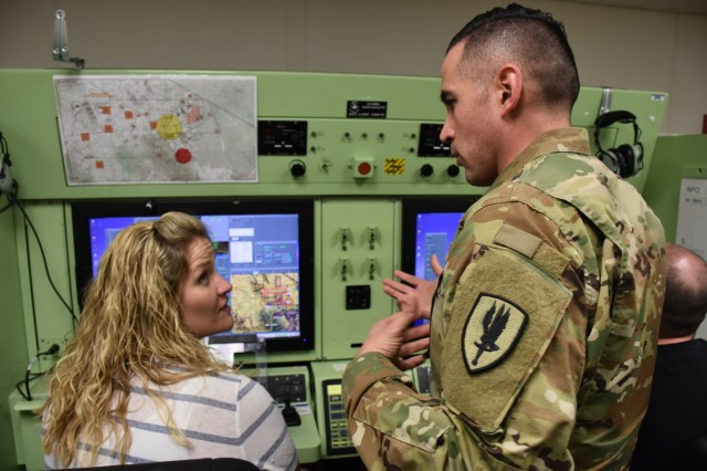 Staff Sgt. Christopher Nakanishi, unmanned aerial system instructor, discusses how to properly zoom in on targets to Kelly Sandbrink, United Services Organization director, during a demonstration of the UAS features, April 11, Fort Huachuca, Ariz. (U.S. Army Photo by Alun Thomas, USAREC Public Affairs)