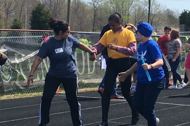 Blanchfield Army Community Hospital Soldier Sgt. Norma Arevalo and Northeast Middle School education assistant Janet Hildebrandt encourage a student-athlete participating in the 100-yard dash at the Special Olympics of Greater Clarksville Spring Games, April 13. The games were held at Kenwood High School and featured track and field events for participants from Montgomery and Houston counties. Soldiers from Blanchfield and Fort Campbell's Warrior Transition Battalion volunteered and helped competitors get to their individual events. U.S. Army photo by Staff Sgt. Victoria Romero.