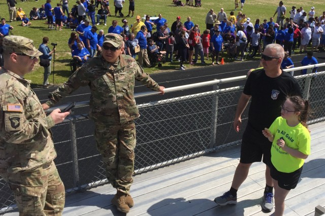 Fort Campbell Warrior Transition Battalion staff, 1st Sgt. Steve Peters and his daughter Abbigail, talk with Soldiers from the Battalion who came out to support Abbigail and other student-competitors from her school at the Special Olympics of Greater Clarksville Spring Games, April 13. Abbigail took first place in the Softball Throw and third place in the 50 meter run. Soldiers from Blanchfield and Fort Campbell's Warrior Transition Battalion cheered on participants and helped competitors get to their individual events. U.S. Army photo by Sgt. 1st Class Elizabeth Mercedes.