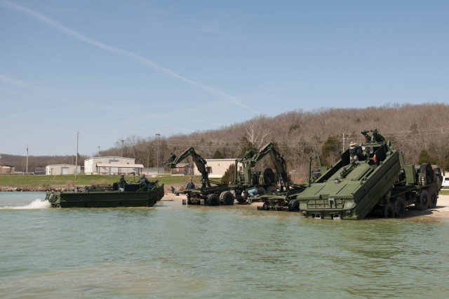 An M30 prepares to be loaded for transport, as another M30, right, is loaded into the lake at Training Area 250.