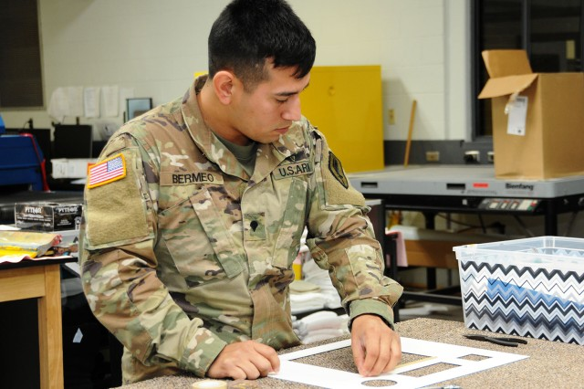 Spc. Henry Bermeo, 1st Battalion, 145th Aviation Regiment, works on a framing project at the Fort Rucker Arts and Crafts Center last year.