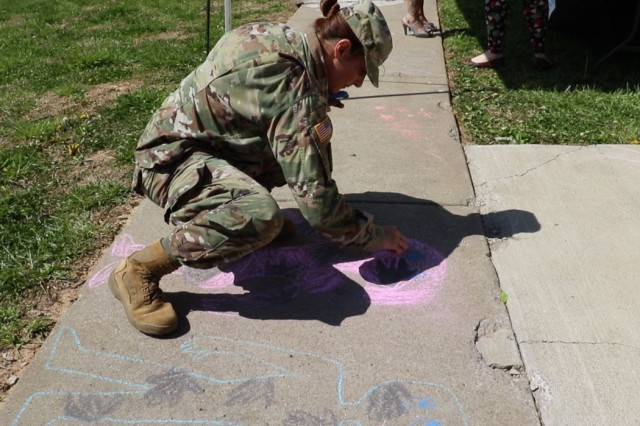 Blanchfield Army Community Hospital Social Worker, 1st Lt. Estela Schlund, draws a man and a woman each covered in handprints representing the emotional scars that sexual assault and sexual harassment can leave on victims. Soldiers and civilians on post participated in Chalk the Walk at Blanchfield April 12 in support of Sexual Assault Awareness and Prevention Month. Participants filled the sidewalk in front of the hospital with messages of support and called on all Soldiers and civilians to help eliminate sexual assault and sexual harassment. U.S. Army photo by Maria Yager.