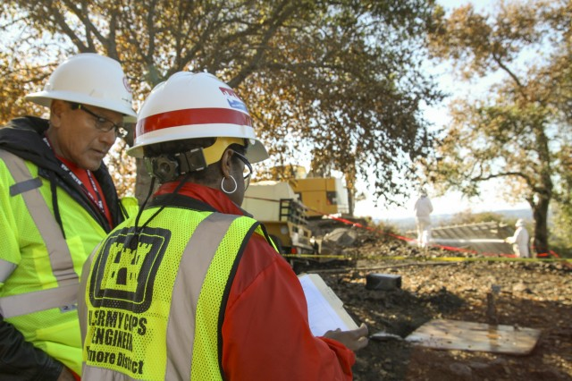 Joe Aguirre (left), a rehired annuitant and LaNesha Mincey, with the Baltimore District, U.S. Army Corps of Engineers, check on the progress of debris removal from a property damaged during the October wildfires in Napa, California on Nov. 17, 2017.