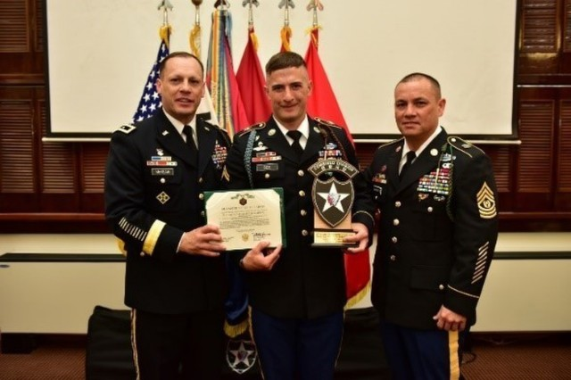 The junior enlisted winner, Cpl. Jacob Bee (center), a native of Naples, Florida, assigned to 1st Battalion, 7th Infantry Regiment, 1st Armored Brigade Combat Team, displays his award and trophy with Brig. Gen. Scott McKean and Command Sgt. Maj. Phil K. Barretto, 2nd Infantry Division/ROK-US Combined Division command team, at the 2018 Best Warrior Competition Awards Ceremony, Camp Red Cloud, Korea, April 15. The 2nd Infantry Division/ROK-U.S. Combined Division conducted a weeklong Best Warrior Competition to identify and recognize the most outstanding officer, warrant officer, non-commissioned officer, junior enlisted Soldier, and Korean Augmentation To the United States Army (KATUSA) within the division.