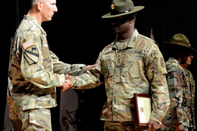 Col. Daniel Ruder, 15th Regimental Signal Brigade commander, congratulates each drill sergeant during a ceremony held April 13 at Alexander Hall.