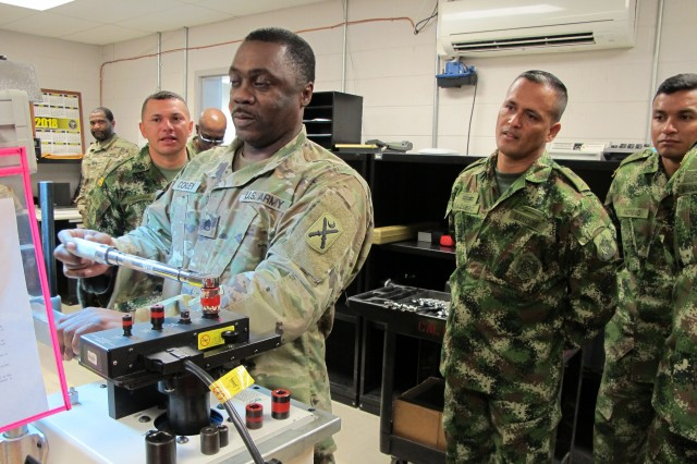 U.S. Army Staff Sgt. Michael Corley, a calibration technician assigned to the South Carolina Army National Guard's Combined Support Maintenance Shop located at McEntire Joint National Guard Base, S.C., demonstrates calibrating tools to soldiers from the Colombian Army during a State Partnership Program subject matter expert exchange on maintenance April 16, 2018.