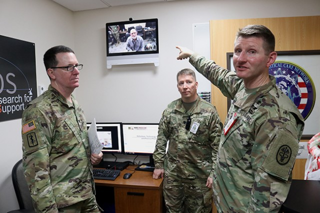 "Lt. Col. Jeremy Pamplin, director of Madigan Army Medical Center's Virtual Critical Care Center, points to the ""Doc Box"" and his counterpart at the Naval Medical Center San Diego as he describes the current capabilities of the system to Col. John Kent, Madigan deputy commanding officer, and Lt. Col. Eric Drynan, Madigan chief of the Information Management Division, and others gathered for the opening of the VC3 April 18 at Madigan on Joint Base Lewis-McChord, Washington."