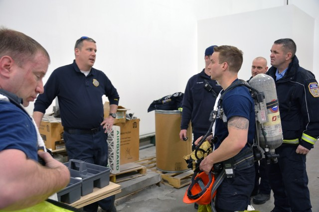 New York State Fire Prevention and Control team member, second from left, providing feedback to Watervliet Arsenal firefighters.