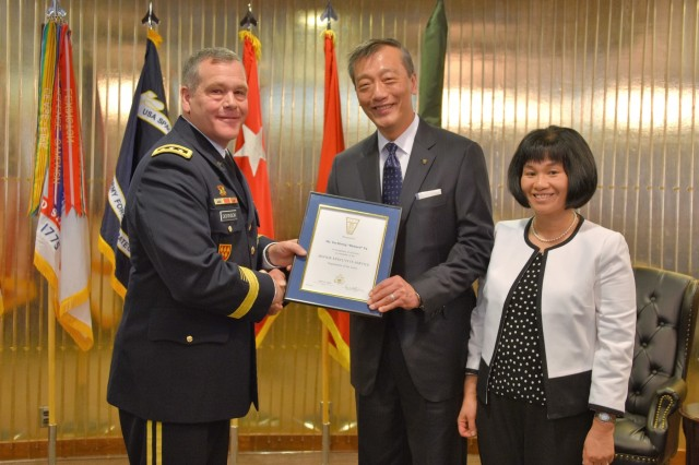 "Lt. Gen. James H. Dickinson, commanding general, U.S. Army Space and Missile Defense Command/Army Forces Strategic Command, presents Tse-Horng ""Richard"" Yu, USASMDC/ARSTRAT Future Warfare Center's new director for Capability Development Integration Directorate, with a Senior Executive Service certificate during his appointment ceremony to SES April 19 at the Club at Peterson Air Force Base, Colorado. Yu's wife of 27 years, Amy, joins her husband during the presentation."