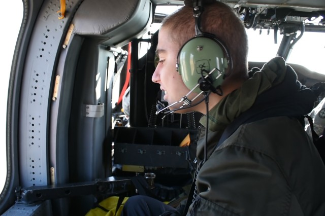 Seth Cummings, a Topeka West high school student, sits in a crew chief seat of a UH-60 Black Hawk helicopter.