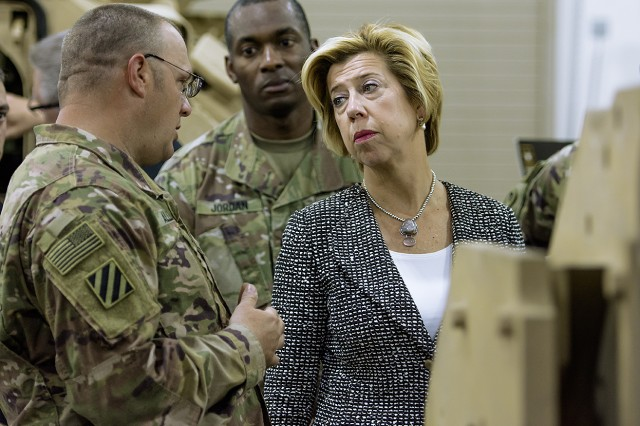 Staff Sgt. Anthony Allen, maintenance quality assurance specialist, Army Field Support battalion-Kuwait discusses the M2A3 Bradley Fighting Vehicle platform with Ellen M. Lord, under secretary of defense for acquisition, technology and logistics, during a tour of an Army Prepositioned Stocks-5 warehouse at Camp Arifjan, Kuwait, April 20. (U.S. Army Photo by Justin Graff, 401st AFSB Public Affairs)