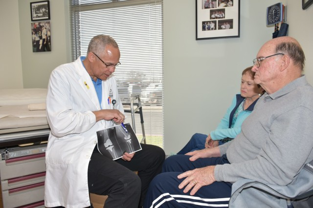 U.S. Army Reserve Col. Paul Phillips III (far left), part of the Orthopedic Surgery team at Hill Country Memorial Medical Group in Fredericksburg, Texas, explains X-ray results to patient, Don Huston (far right), 77, and his wife, Alice, 78, of Boerne, during a clinic visit March 14.  Phillips, an orthopedic surgeon and 23-year Reserve veteran, also serves as chief of Professional Services with the 228th Combat Support Hospital at Joint Base San Antonio-Fort Sam Houston.