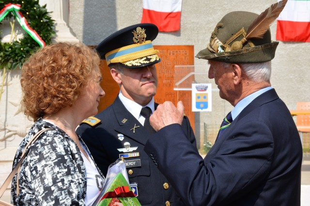 VICENZA, Italy (April 25, 2018) - USAG Italy Garrison Commander Col. Erik Berdy talks to an Italian World War II Alpini veteran and USAG Italy Public Affairs Specialist Anna Ciccotti interprets following an Italian Liberation Day celebration.  Berdy and Command Sgt. Major Mason Bryant joined mayors from six towns in Mason Vicentino to mark the 73rd anniversay of Italian Liberation Day.  Liberation Day (Festa della Liberazione) remembers Italians who fought against the Germany and Mussolini's troops during World War II. More than 300 attended the ceremonies including veterans of World War II, Italian Alpini chapters, school groups and a community band.  Mayor of Mason Vicentino Massimo Pavan thanked the U.S. Army officials and on behalf of the other five mayors, expressed thanks for the support and friendship between the Italian and American communities.