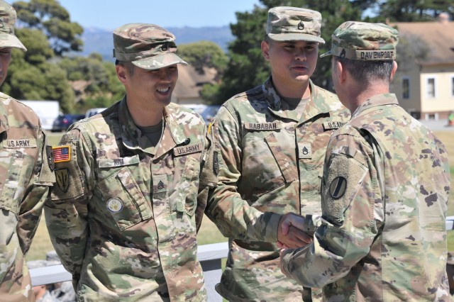 Staff Sgt. Alex Rababah (right), an Arabic Military Language Instructor at the Defense Language Institute Foreign Language Center, Presidio of Monterey, shakes hands with Command Sgt. Maj. David Davenport, the senior enlisted leader for the U.S. Army Training and Doctrine Command, June 16, 2017. Davenport congratulated Rababah for being named MLI of the quarter at the institute. Rababah would go on to be named the TRADOC Instructor of the Year in the non-commissioned officer category for 2017. (U.S. Army photo by Patrick Bray/Released)