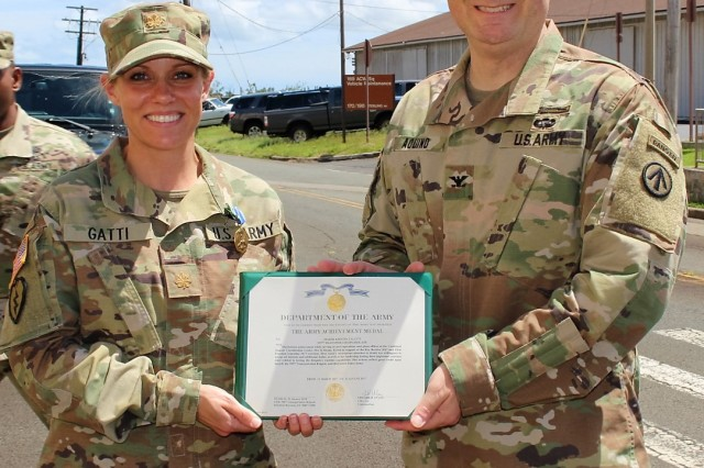Reserve Maj. Kristin Gatti, receives an Army Commendation Medal for work as an IMA from 599th deputy commander for mobilization, Col. Anthony Aquino, during a ceremony in front of brigade headquarters on April 18.