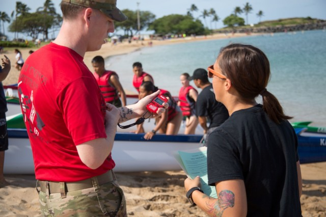 A Soldier with 65th Brigade Support Battalion, 2nd Infantry Brigade Combat Team, 25th Infantry Division confers with the score keeper about the time it took a set of cadets from Oahu's Junior Reserve Officers Training Corps to complete a canoe race at the Pililaau Army Recreation Center, Hawaii April 21, 2018 during the 13th Annual Waianae Adventure Challenge. This event is a multi-day team physical fitness challenge to hone their skills of leadership and camaraderie. Soldiers from 2IBCT, 25ID helped grade, coach and cheer on these young adults. (U.S. Army Photo by 1st Lt. Ryan Debooy)