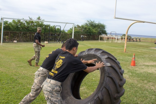 """Cadets from Oahu's Junior Reserve Officers Training Corps participate in a tire flip station at Waianae High School, Waianae, Hawaii April 22, 2018 during the 13th Annual Waianae Adventure Challenge. This event is a multi-day team physical fitness challenge to hone their skills of leadership and camaraderie. """"They're learning the importance of being in charge and setting the pace for everything that the team does,"""" said Staff Sgt. Keith Vinson, a Soldier with B Company, 1st Battalion, 27th Infantry Regiment, 2nd Infantry Brigade Combat Team, 25th Infantry Division. Soldiers from 2IBCT, 25ID helped grade, coach and cheer on these young adults. (U.S. Army Photo by Staff Sgt. David Beckstrom)"""