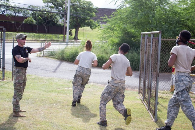 A Soldier with 2nd Infantry Brigade Combat Team, 25th Infantry Division directs cadets from Oahu, Alaska and California's Junior Reserve Officers Training Corps toward the finish line during the cross country race portion of the 13th Annual Waianae Adventure Challenge April 22, 2018. This event is a multi-day team physical fitness challenge to hone their skills of leadership and camaraderie. Soldiers from 2IBCT, 25ID helped grade, coach and cheer on these young adults. (U.S. Army Photo by Staff Sgt. David Beckstrom)