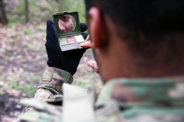 U.S. Army Spc. Christian Summers, assigned to Bravo Company, 44th Expeditionary Signal Battalion, 2nd Theater Signal Brigade, looks in the mirror as he applies comouflage paint during exercise Stoney Run, April 24, 2018 in the Sennelager Training Area, Germany. Stoney Run is an annual U.S.-U.K. signal exercise designed to test and validate communications and network capabilities, and enhance interoperability and partner capacity between the two NATO allies.