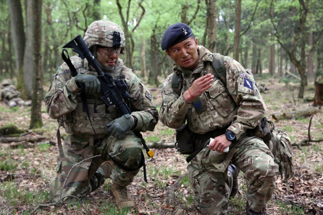 British Army Sgt. Thapa Kumar, assigned to the 250th Signal Squadron, Queen's Gurkha Signals, instructs U.S. Army Staff Sgt. Jeffery Lamb, assigned to Bravo Company, 44th Expeditionary Signal Battalion, 2nd Theater Signal Brigade, during a joint tactical patrol during exercise Stoney Run in the Sennelager Training Area, Germany, April 24, 2018. Stoney Run is an annual U.S.-U.K. signal exercise designed to test and validate communications and network capabilities, and enhance interoperability and partner capacity between the two NATO allies.
