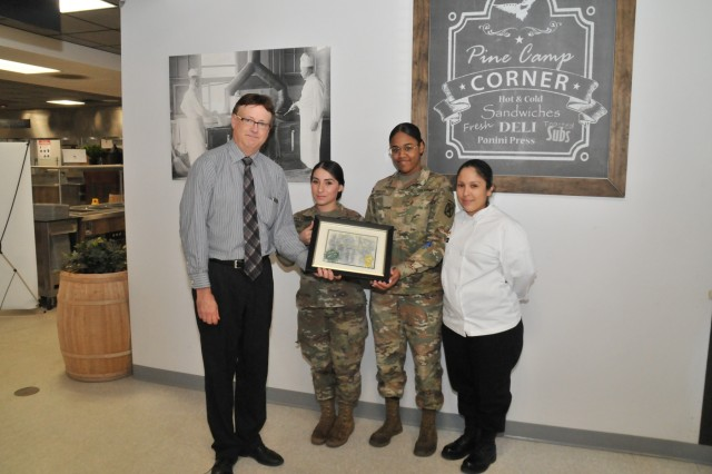 The team from 2nd Brigade Combat Team's Commando Café receive certificates of achievement from Jim Miller, Environmental Division chief, on April 24 for winning the inaugural Earth Day Cake Bake-Off. The winning team included Spc. Natalia Diaz-Henao, Pvt. Alyssa K. Sealey, Staff Sgt. Cynthia I. Hicks and (not pictured) Staff Sgt. Norma Roberts.