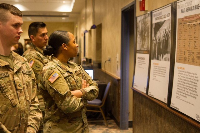 Attendees at the Holocaust Remembrance Ceremony on April 24 take the time to look at the historical displays on the walls of the Commons. (Photo by Staff Sgt. James Avery, 1st Brigade Combat Team Public Affairs)