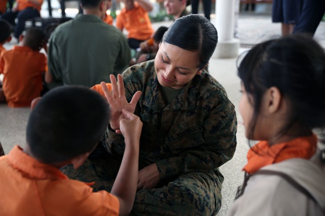 Lance Cpl. Sherry L. Eaton sits with children from Nakhon Ratchasima Panyonnookun School during a community outreach event February 12. The school provides education for 295 children with disabilities such as autism, Down syndrome, hearing loss, and attention deficit hyperactivity disorder.